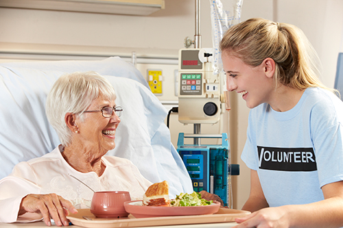 Patient receiving food in hospital from a volunteer